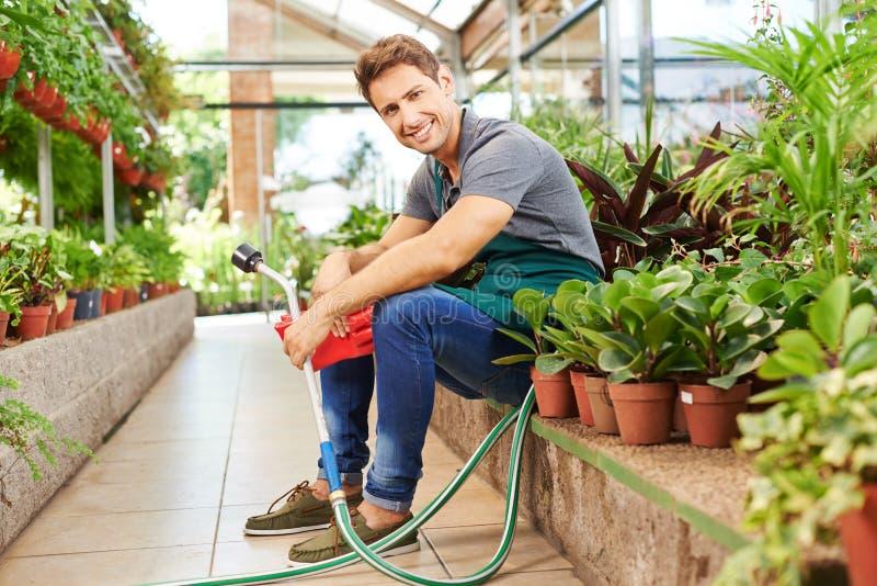 Jardinero que se sienta entre las plantas en tienda del cuarto de niños imágenes de archivo libres de regalías