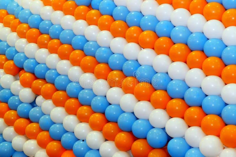 Jardines de globos de color naranja, azul y blanco foto de archivo