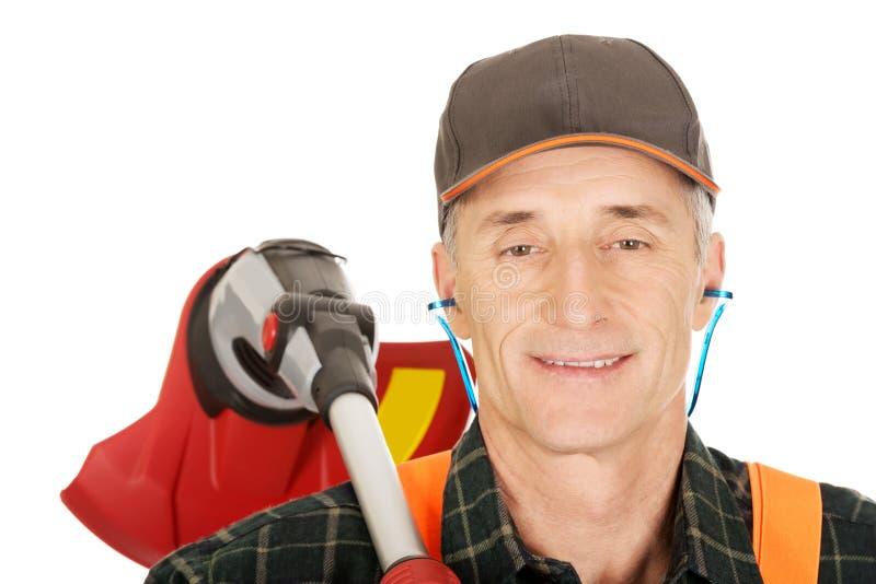 Jardinier avec le trimmer et les protecteurs auriculaires photo stock