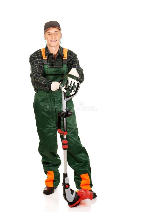 Jardinier avec le trimmer et les protecteurs auriculaires image stock