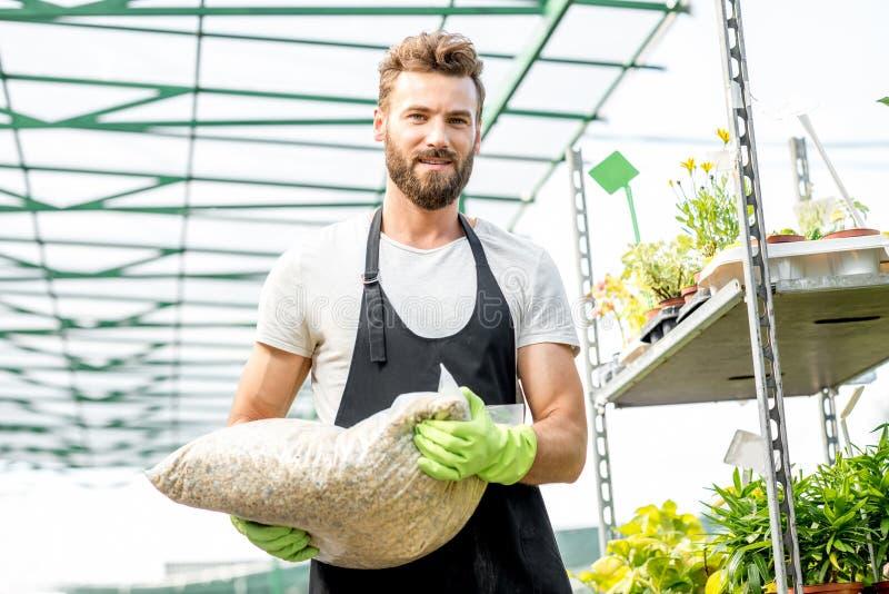 Jardinier beau avec le sac du sol photo libre de droits