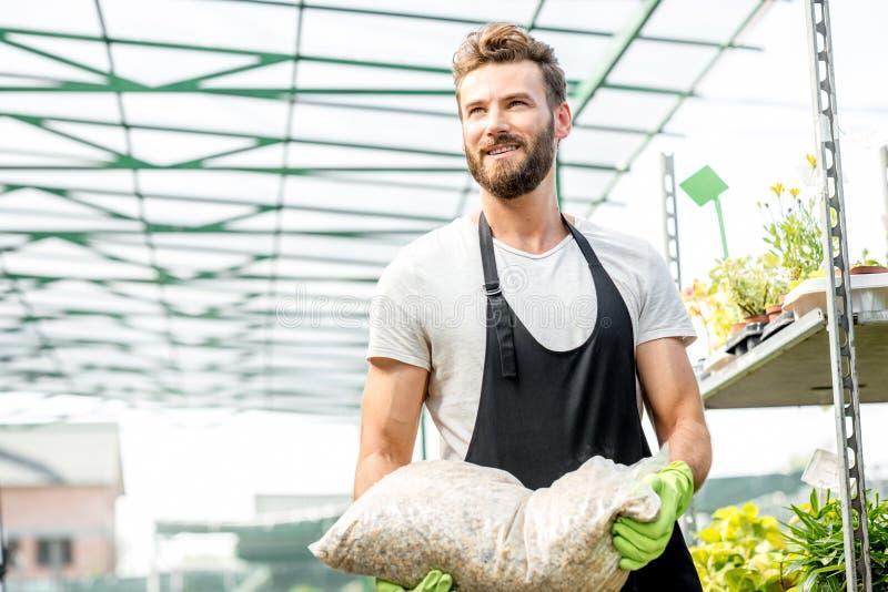 Jardinier beau avec le sac du sol image libre de droits