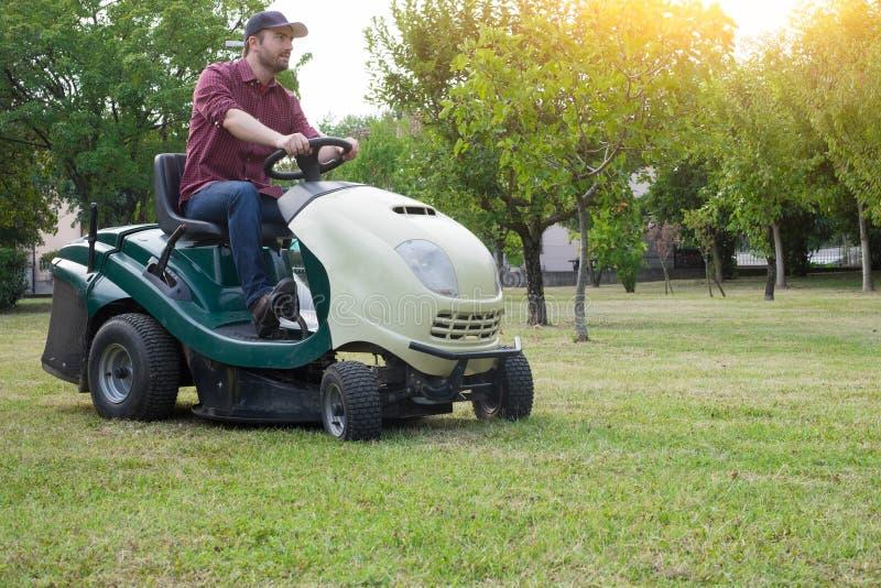 Jardinier coupant l'herbe d'un jardin posé sur une tondeuse à gazon image stock