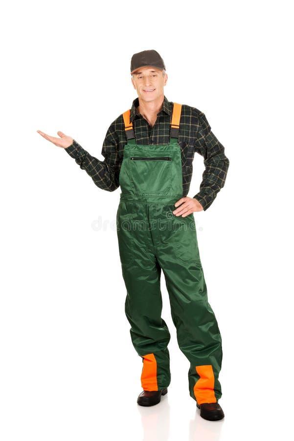 Jardinier dans l'uniforme montrant l'espace du côté gauche photos libres de droits