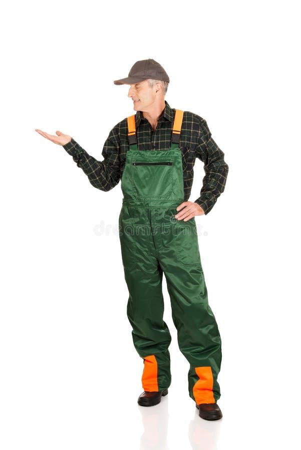 Jardinier dans l'uniforme montrant l'espace du côté gauche photographie stock libre de droits