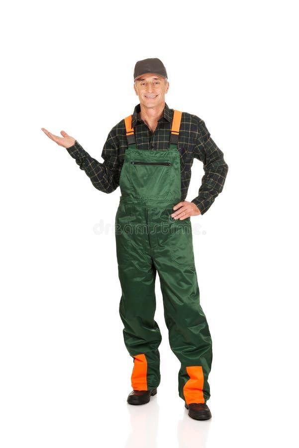 Jardinier dans l'uniforme montrant l'espace du côté gauche image libre de droits