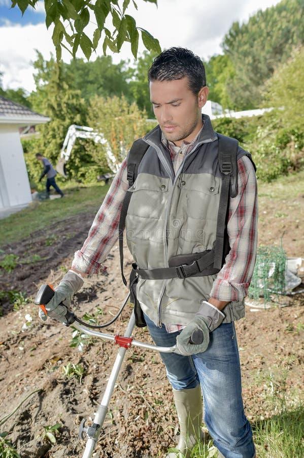 Jardinier employant un strimmer photo libre de droits