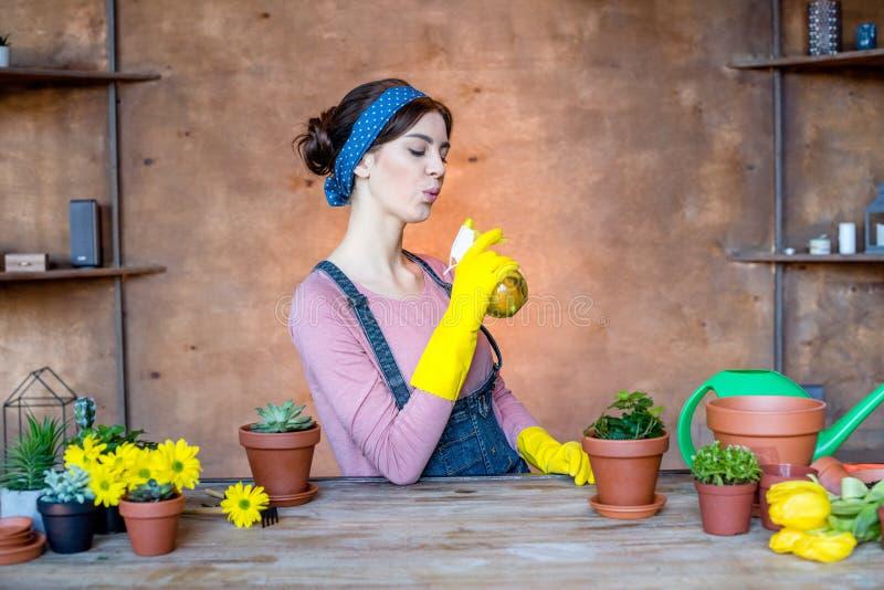 Jardinier féminin avec la bouteille de jet photographie stock