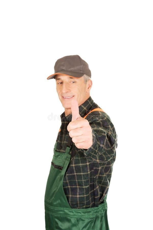 Jardinier mûr dans l'uniforme avec des pouces  photographie stock libre de droits