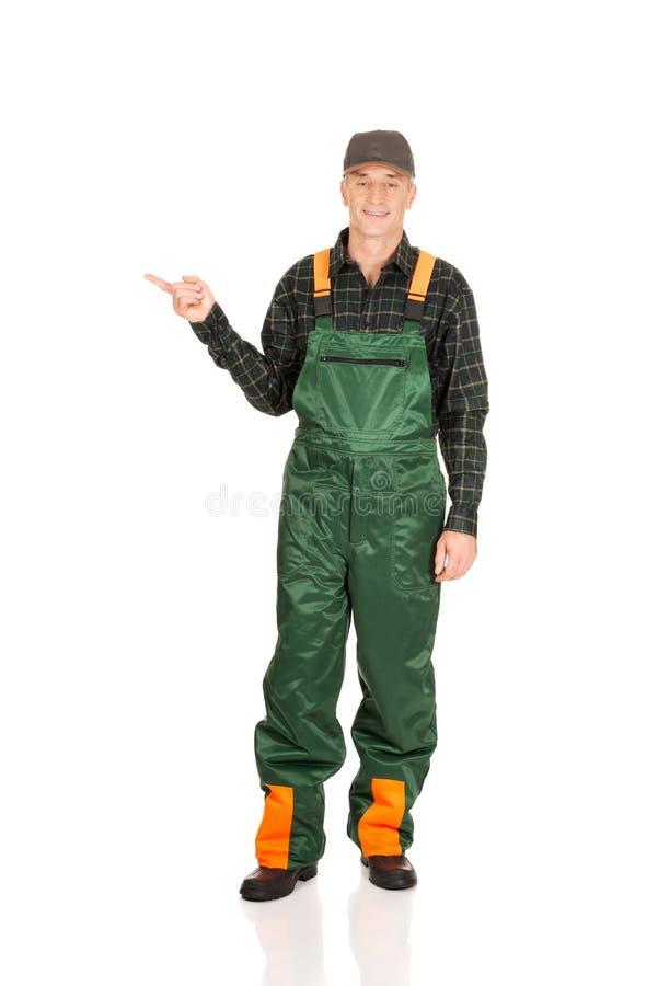 Jardinier mûr dans l'uniforme indiquant la gauche image stock
