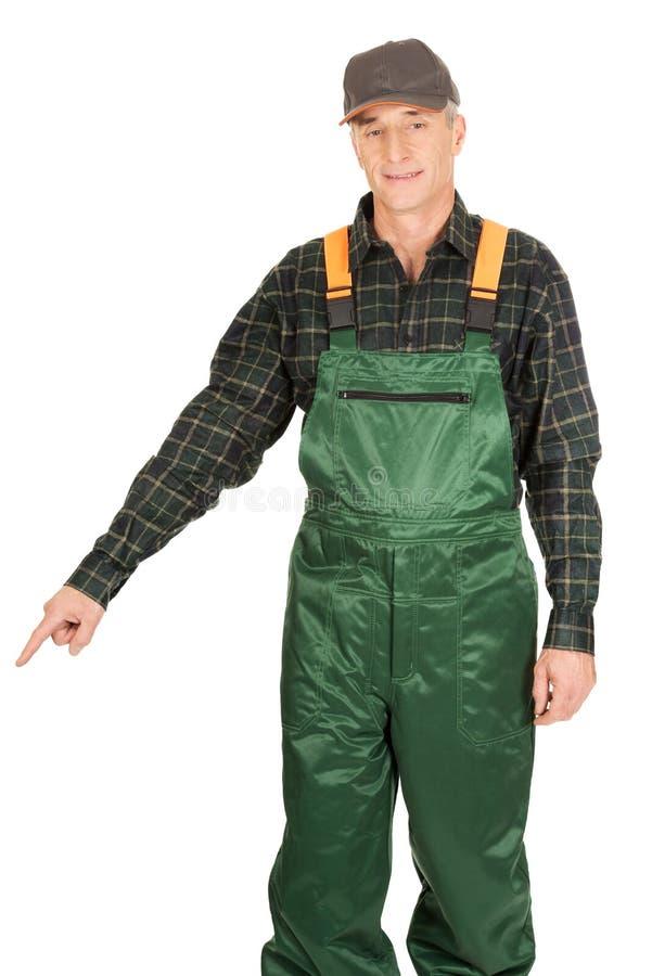 Jardinier mûr dans l'uniforme se dirigeant vers le bas photos stock