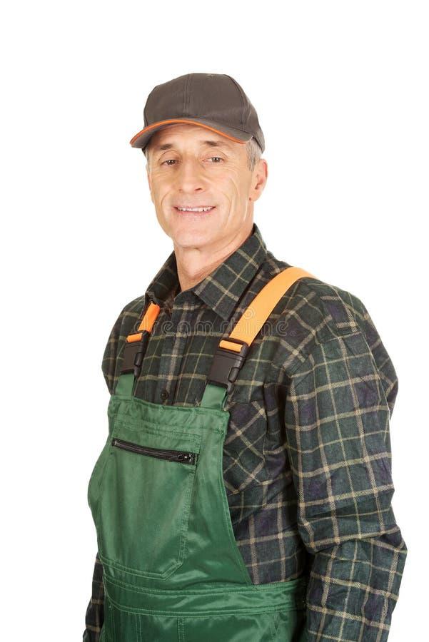 Jardinier mûr se tenant dans l'uniforme photo libre de droits