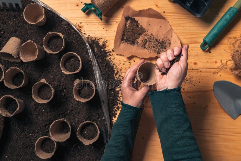 Jardinier remplissant conteneur biod?gradable de pot de sol photographie stock