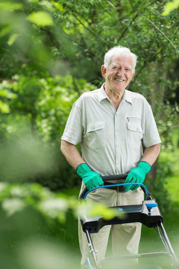 Jardinier supérieur fauchant l'herbe image libre de droits