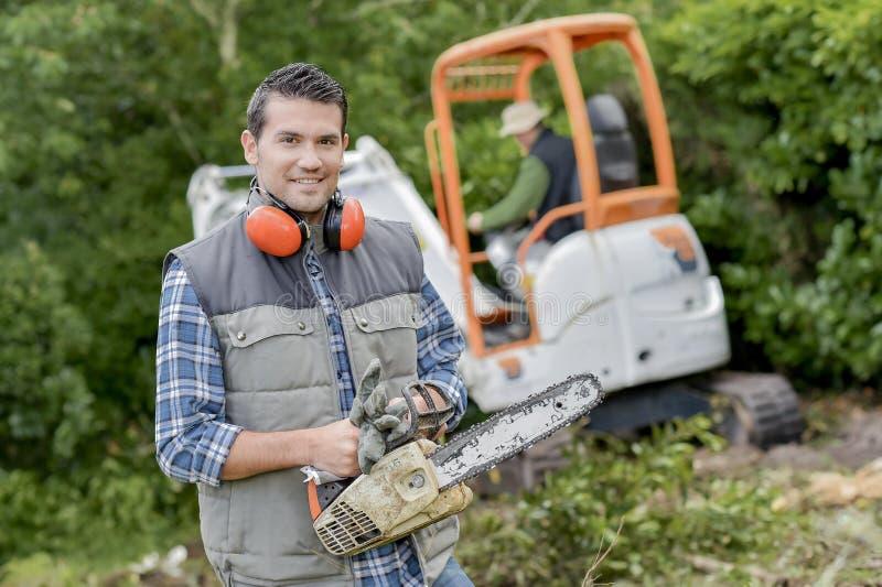 Jardinier tenant une tronçonneuse photos libres de droits