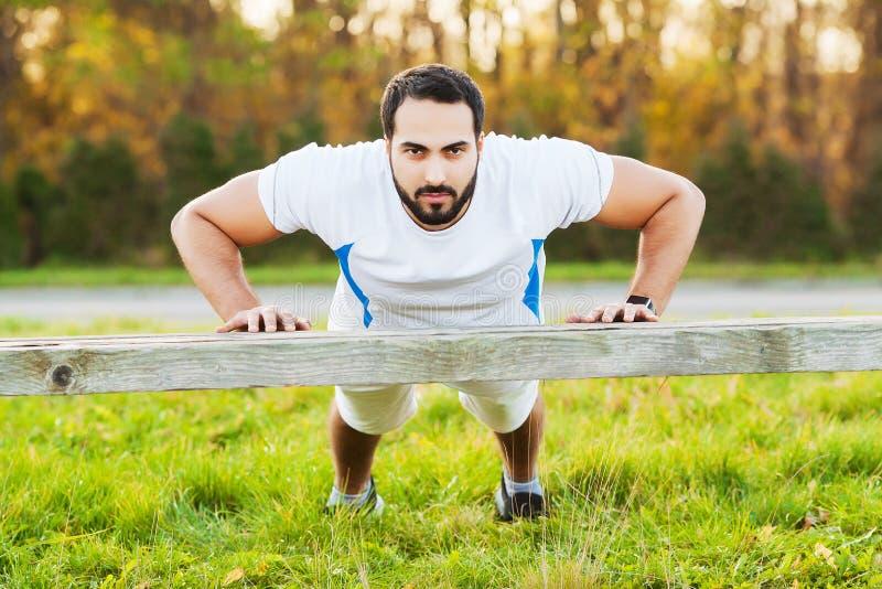 Jaren '30 van de portret de sportieve mens in sportkleding die opdrukoefeningen in groen park doen stock afbeelding