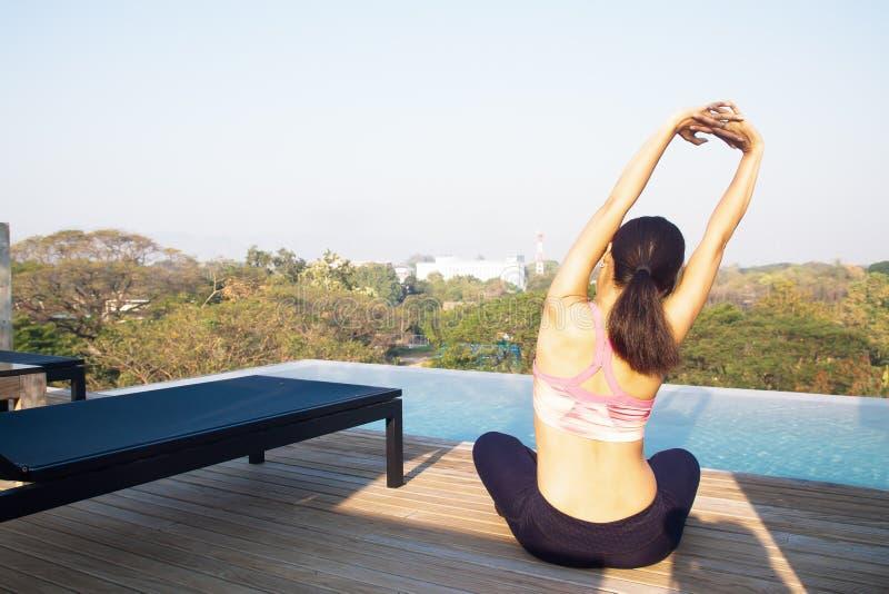 jaren '40vrouw die yoga dichtbij zwembad op de dakbovenkant doen Gezond levensstijlconcept royalty-vrije stock afbeelding