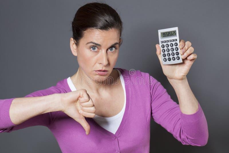 jaren '30vrouw door cijfers wordt op haar calculator worden getoond teleurgesteld die stock afbeelding