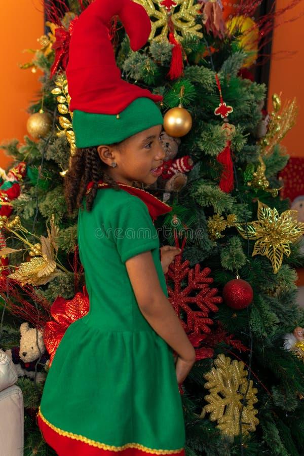 5-jarige Afro-Colombiaanse Colombiaanse Latino-meisje, verkleed als een elf naast de kerstboom stock fotografie