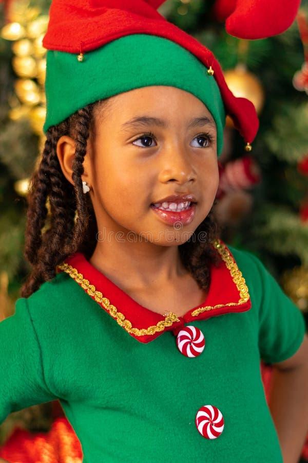 5-jarige Afro-Colombiaanse Colombiaanse Latino-meisje, verkleed als een elf naast de kerstboom stock foto