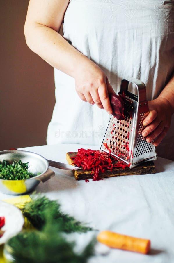 Jarosze i kucharstwo Damy wręczają cięciu zielonego warzywa, przygotowywającego obraz stock