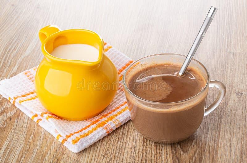 Jarra con leche en la servilleta, cacao con la leche, cuchara en taza en la tabla de madera foto de archivo