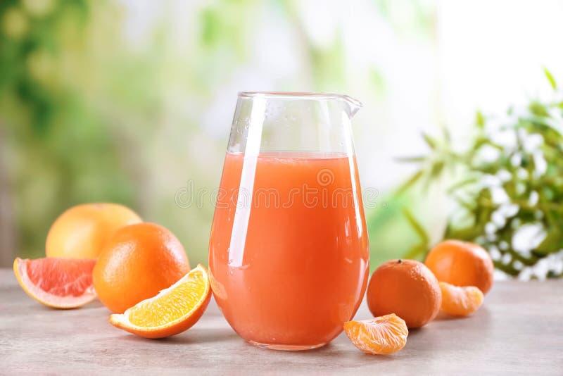 Jarra de cristal con el jugo y las frutas de la fruta c?trica en la tabla imagenes de archivo