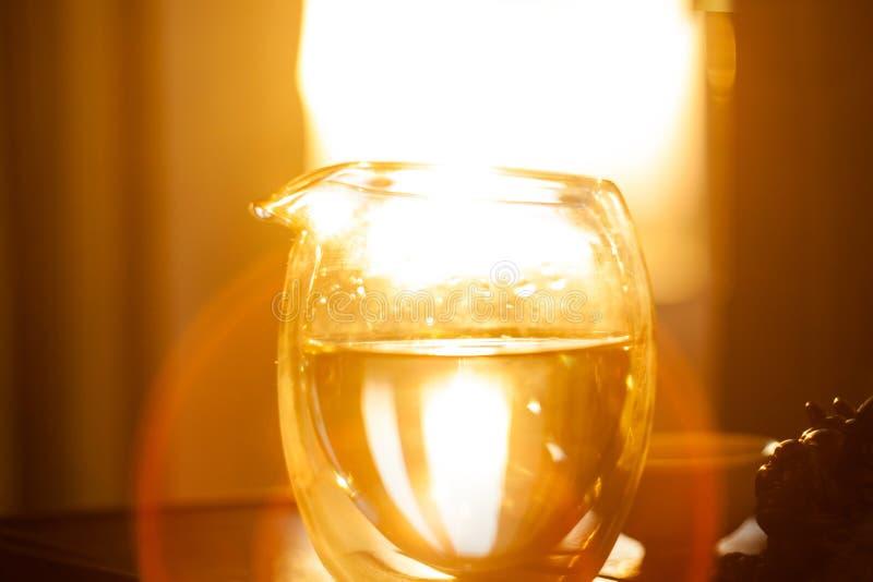 Jarra de cristal de té caliente en la tabla de madera en el fondo de la puesta del sol hermosa con los rayos del sol fotografía de archivo