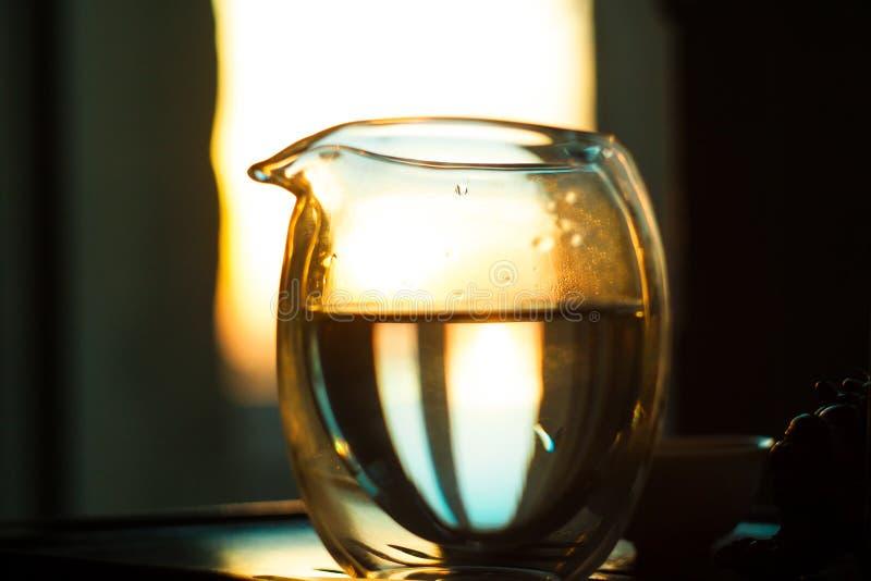 Jarra de cristal de té caliente en la tabla de madera en el fondo de la puesta del sol hermosa con los rayos del sol foto de archivo