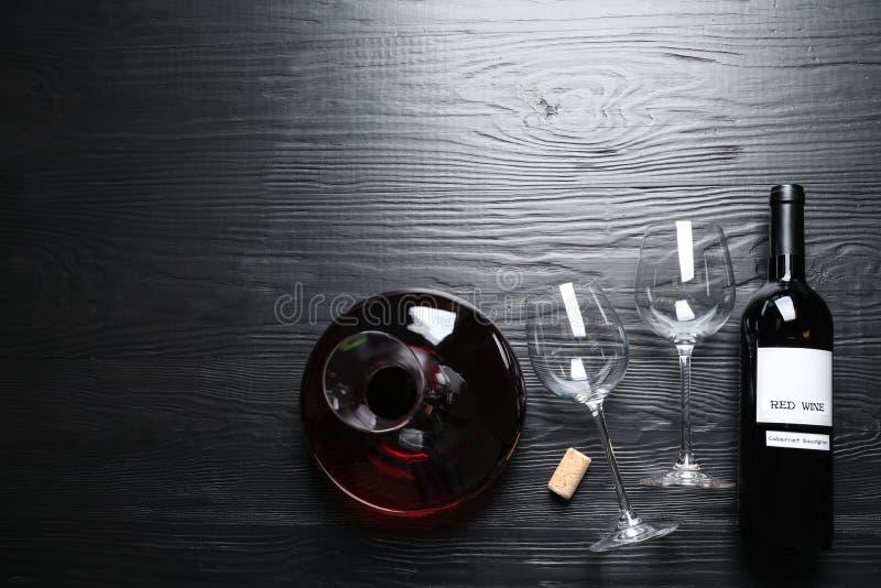 Jarra, vidrios y botella con el vino tinto en el fondo de madera, endecha plana fotos de archivo libres de regalías