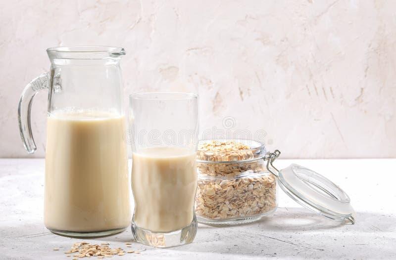 Jarra y vidrio transparentes de la leche y del tarro de la avena con las escamas de la avena en el fondo blanco imagen de archivo libre de regalías