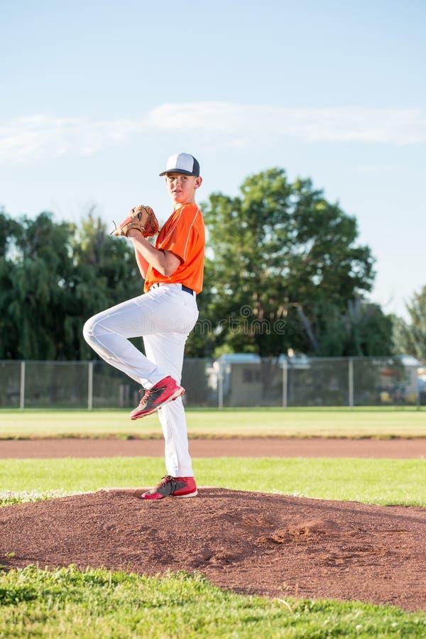 Jarro adolescente no monte do basebol fotografia de stock royalty free