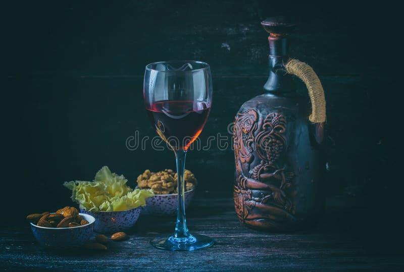 Jarro cerâmico para o vinho, queijo, porcas em uma placa de madeira, fundo imagem de stock
