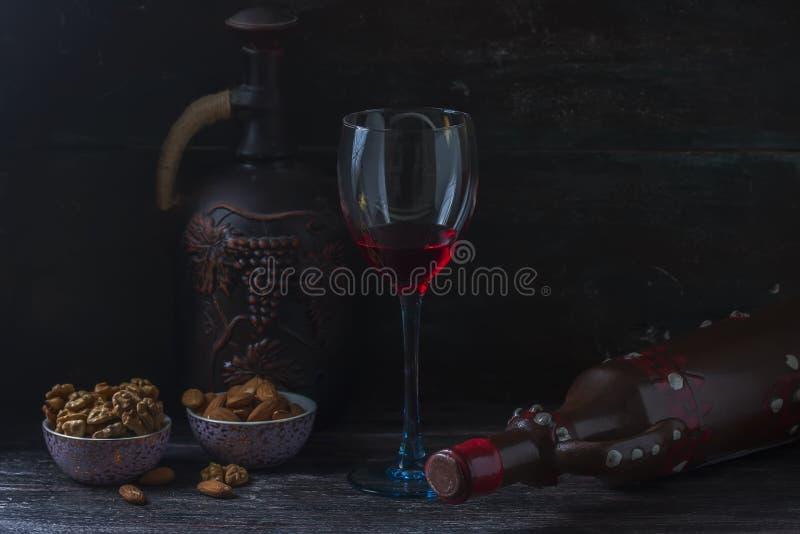 Jarro cerâmico para o vinho, queijo, porcas em uma placa de madeira, fundo foto de stock