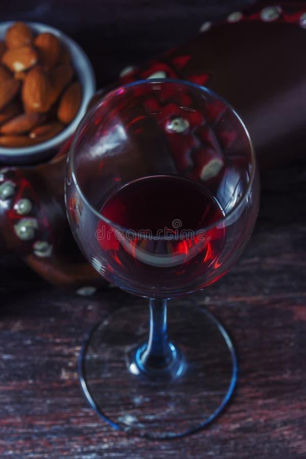 Jarro cerâmico para o vinho, queijo, porcas em uma placa de madeira, fundo fotografia de stock royalty free