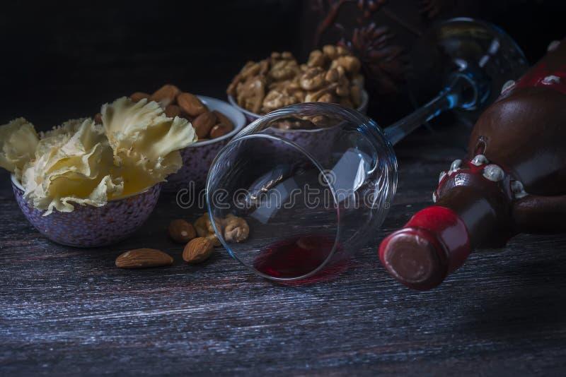 Jarro cerâmico para o vinho, queijo, porcas em uma placa de madeira, fundo imagem de stock royalty free