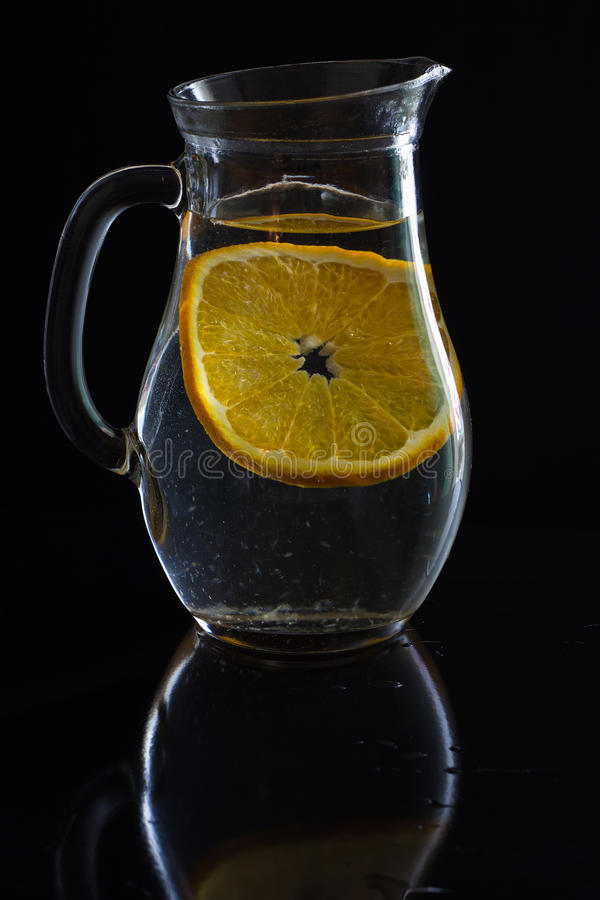 Jarro com água e uma fatia de laranja foto de stock royalty free
