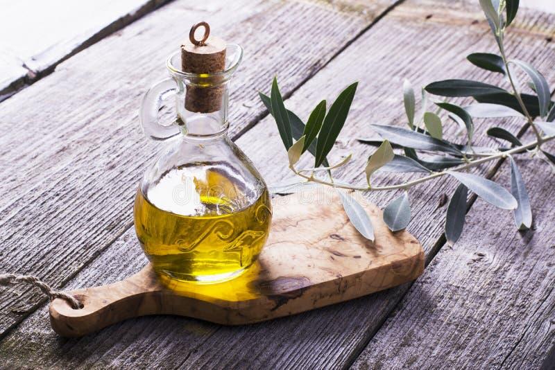 Jarro con aceite de oliva virginal adicional en la tabla de cortar rodeada por las ramas fotografía de archivo libre de regalías