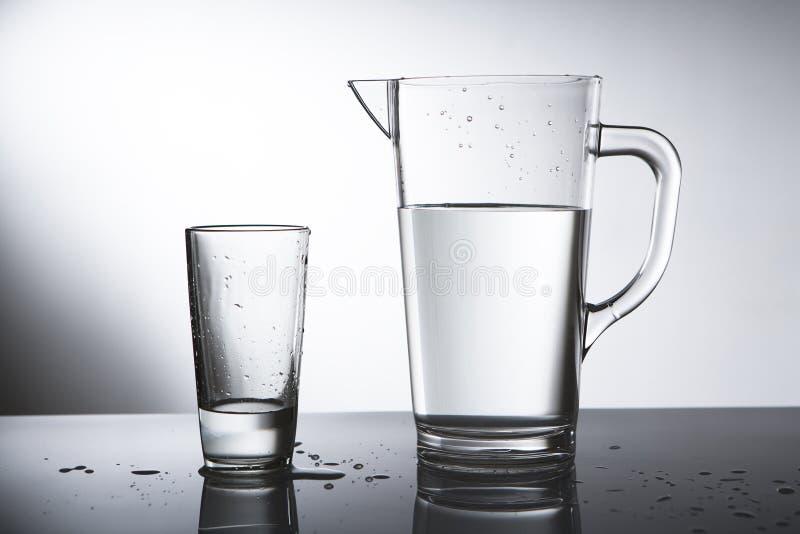 Jarro da água com vidro imagens de stock royalty free