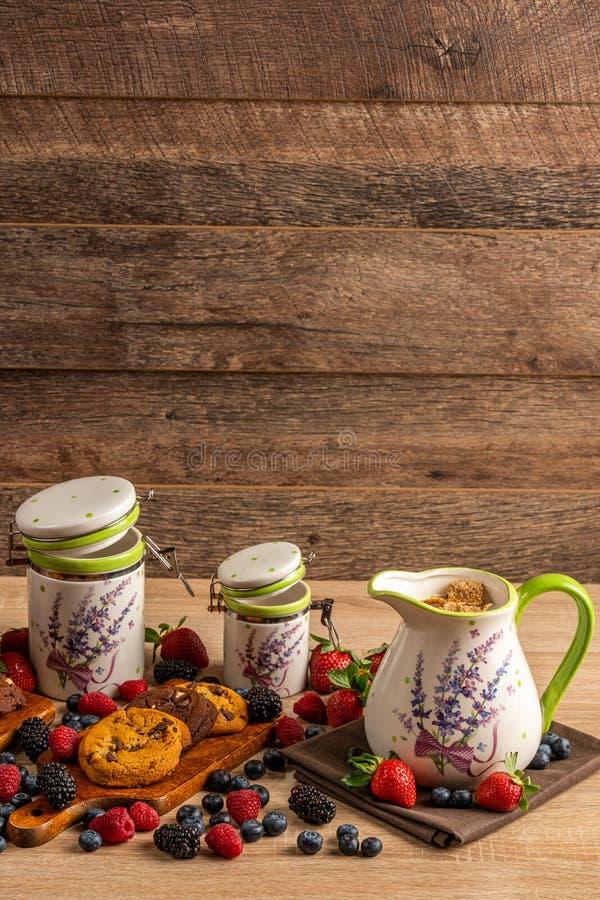 Jarro de cerámica y dos tarros de cerámica del tamaño con las galletas y la mezcla de frutas del bosque en fondo de madera imagen de archivo