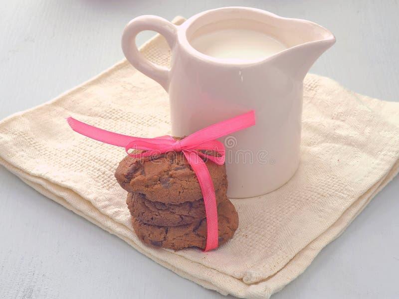 Jarro de leite e chocolate Chip Cookies no fundo de madeira branco foto de stock royalty free