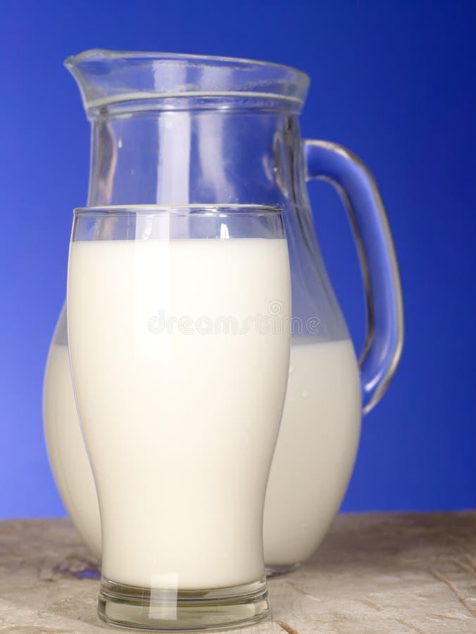 Jarro de leite perto do vidro fotografia de stock royalty free