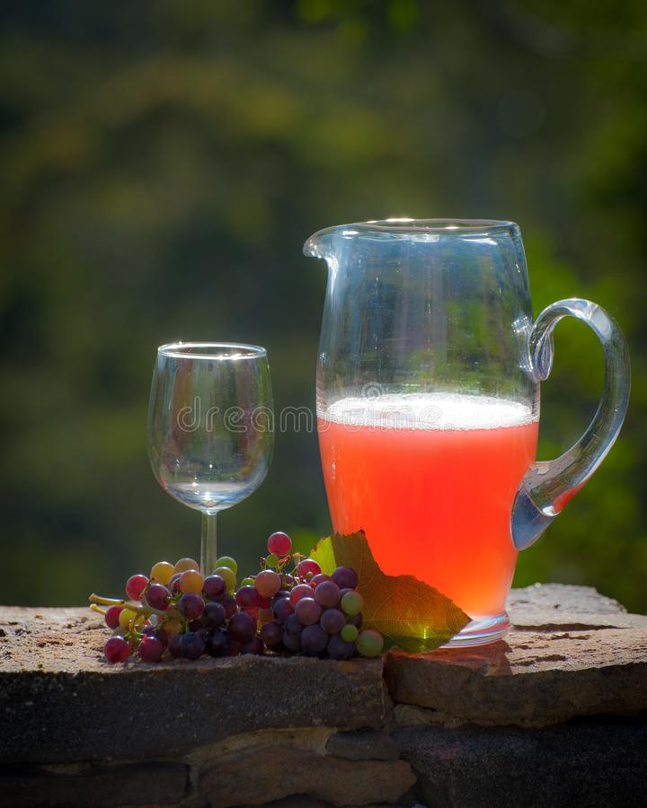 Jarro de suco de uva recentemente espremido colocado em uma parede de pedra com grupo de uvas e de vidro foto de stock