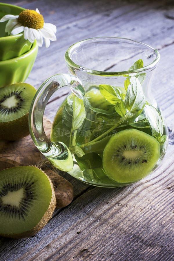 Jarro de vidro com fatias frias do quivi do chá verde e oréganos no fundo cinzento de madeira imagem de stock