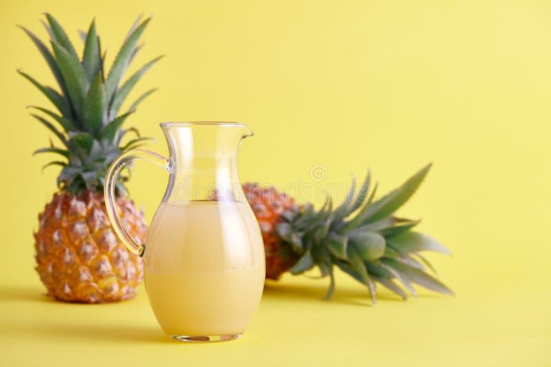 Jarro de vidro de suco de abacaxi fresco no amarelo fotografia de stock