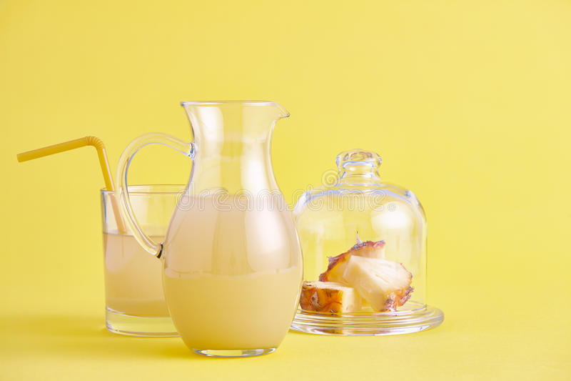 Jarro de vidro de suco de abacaxi fresco no amarelo imagens de stock