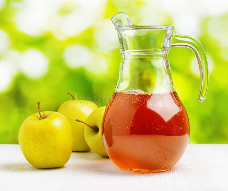 Jarro de zumo de manzana en fondo de la naturaleza foto de archivo