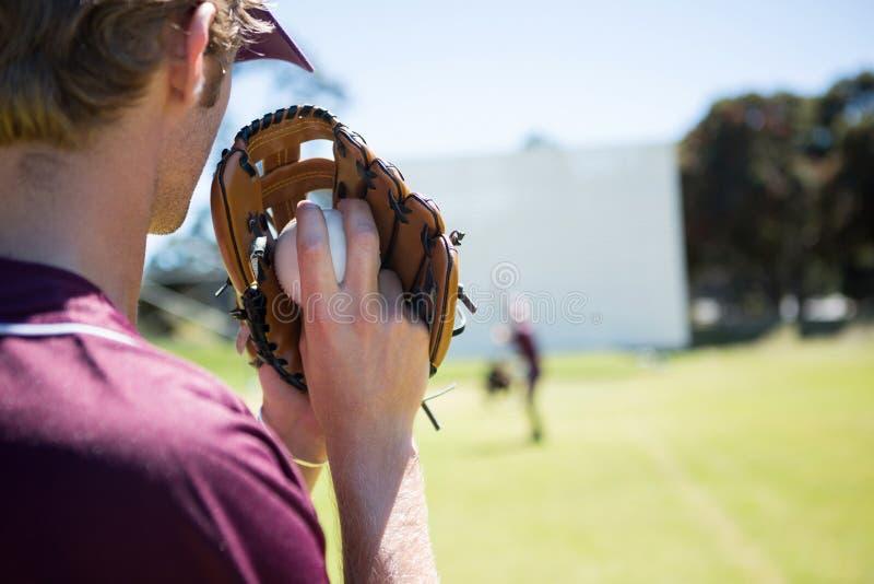 Jarro do basebol que guarda a bola na luva no campo de ação imagens de stock