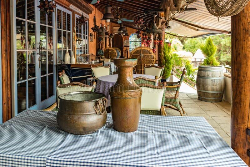 Jarro do vintage e potenciômetro de cobre do jogador em uma tabela com uma toalha de mesa colorida Tambores de vinho de madeira v fotografia de stock