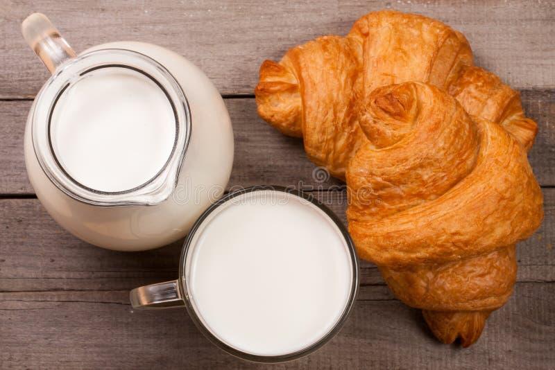 Jarro e um vidro do leite com um croissant em um fundo de madeira Vista superior imagens de stock